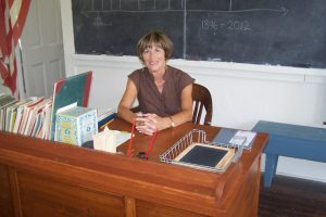 Photo of a schoolhouse volunteer sitting at a desk