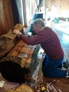 Photo of man working on a tree stump