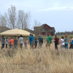 Photo of people walking to a tent in the prairie