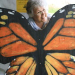 Photo of a woman posing with a monarch caterpillar cutout