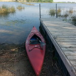 Photo of an empty kayak by a wooden dock