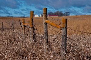 Photo of an old fence with a vivid blue sky