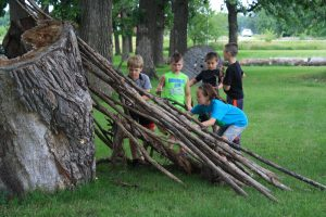 Photo of kids building shelter out of sticks