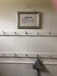 Photo of a sign and bonnet hanging on a hook