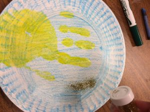 Photo of a yellow handprint on a paper plate with glitter being poured