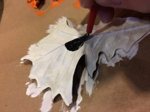 Photo of a white-painted leaf being painted with black