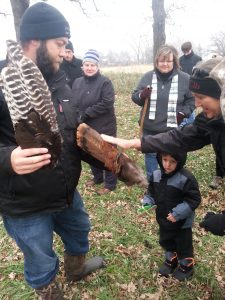 Photo of people touching a turkey feather