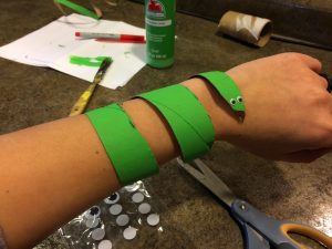 Photo of a snake cuff made from a toilet paper tube around a wrist