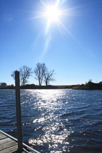 Photo of the sun over a small pond with the corner of the dock in view