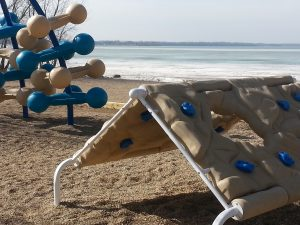 Photo of playground equipment near frozen lake