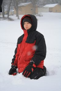 Photo of a boy kneeling in the snow