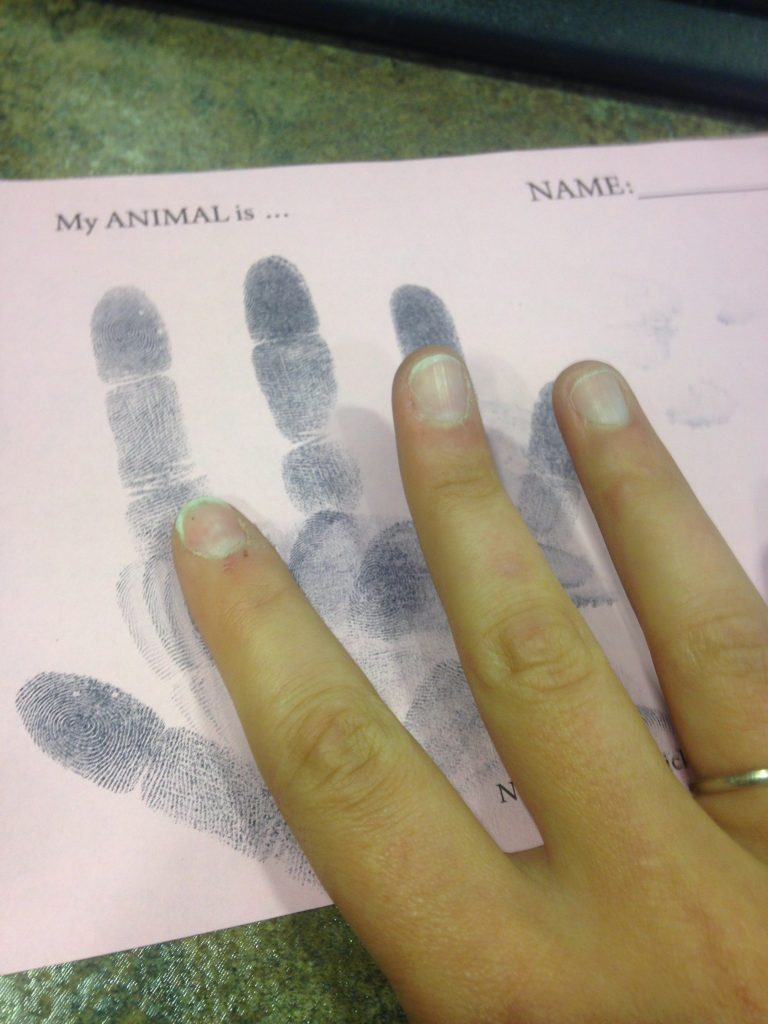 Photo of a person using ink stamp pad to create fingerprint image