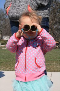 Photo of a girl looking through toilet paper binoculars