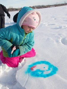 Photo of a girl coloring snow with food coloring