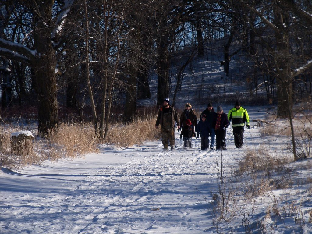people walking on a snowy trail