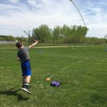 Photo of youth throwing spear with atlatl