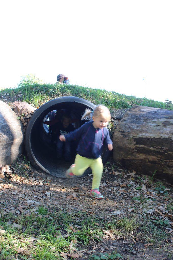 Photo of a child running out of a tunnel
