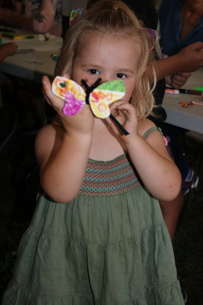 Photo of a little girl holding a butterfly ring