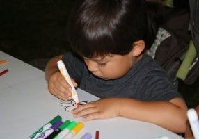 Photo of boy coloring a bee